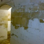 flaking limewash on limestone cellar walls